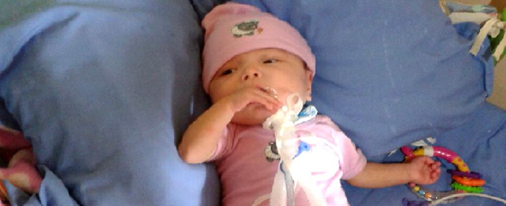 Un bebé acostadito en una cama con su manito en la boca.
