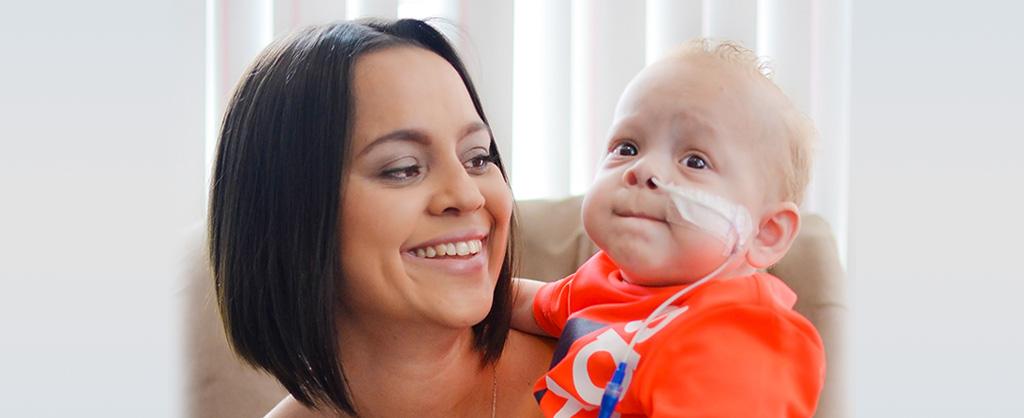 Una madre sostiene a su pequeño hijo quien tiene una sonda en la nariz.